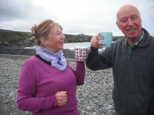 Jan and Rhys smiling on the beach with mugs of tea